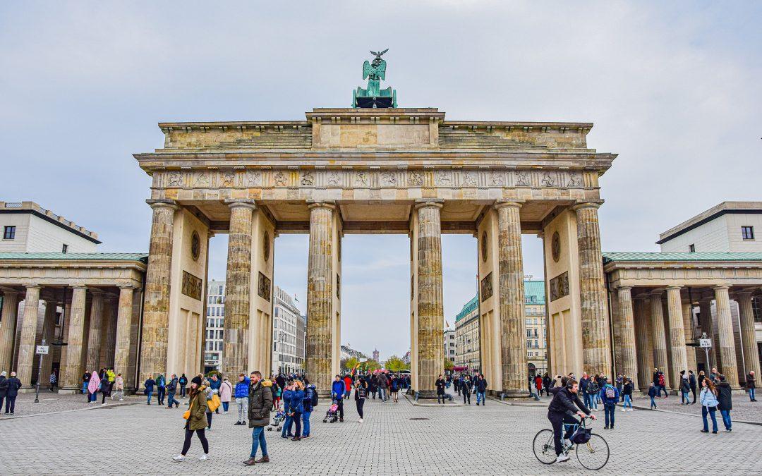 Blick auf das Brandenburger Tor in Berlin, mit Menschen die vorbei gehen.