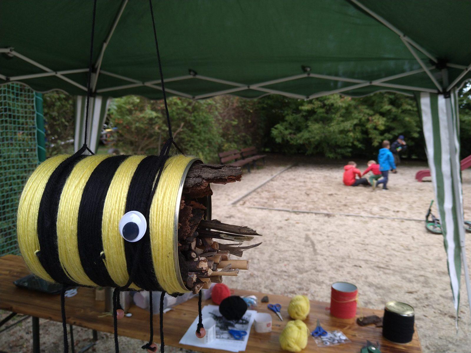 Im Vordergrund ein Insektenhotel das aussieht wie eine Biene